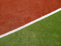 Colorful running track surface. Colorful red and green surface of running track separated by diagonal white line Stock Photography