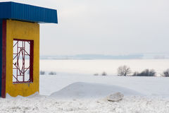 A colorful rural bus stop with snowy meadows in the winter. A colorful rural bus stop with snowy fields in the winter Stock Photography