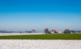 Colorful rural winter landscape. Green vegetation and snow on the plowed fields in a Dutch winter landscape Royalty Free Stock Photography