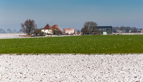 Colorful rural winter landscape. Green vegetation and snow on the plowed fields in a Dutch winter landscape Royalty Free Stock Photo