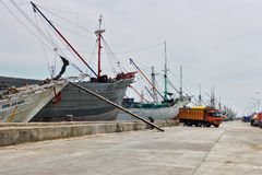 Colorful rusty ship in Jakarta harbor with fishermen on board Stock Photos