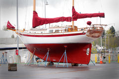 Colorful Sailboat in Dry Dock. A colorful red sailboat sits in dry dock for repair and maintenance Royalty Free Stock Photo