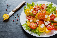 Colorful salad, fresh green leaves and sliced red and yellow cherry tomatoes, white plate, knife, black stone background Royalty Free Stock Photos