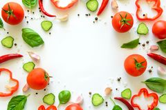 Colorful salad ingredients pattern made of tomatoes, pepper, chili, garlic, cucumber slices and basil on white background. Cooking concept. Top view. Flat lay stock photos