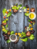 Colorful salad ingredients with tomatoes and feta cheese on rustic blue wooden background, round frame. Top view Royalty Free Stock Photography