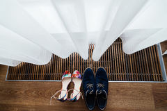 Colorful sandals of the bride and blue shoes of the groom under curtain at the window Royalty Free Stock Image