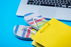 Colorful sandals in shopping bag and cool laptop on the wonderfu Royalty Free Stock Photo