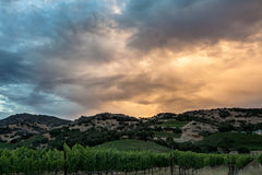 Colorful, saturated clouds during sunset over California hills and vineyard Royalty Free Stock Photos