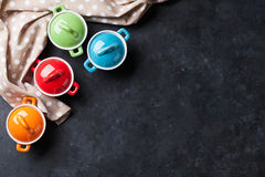 Colorful saucepans on stone Royalty Free Stock Photography