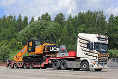 Colorful Scania R560 and JCB Hydraulic Excavator on Trailer stock photos