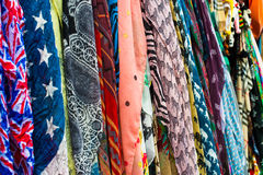 Colorful scarfs. A row of various colorful scarfs hanging on a wall stock photos