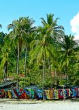 Colorful scarfs for sale. A row of colorful scarfs hanging under palm trees on a beach in Costa Rica Royalty Free Stock Photo