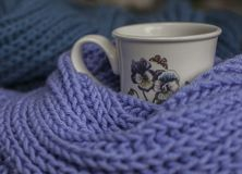 Colorful scarves, violet and blue, and a cup of tea. This image shows two colorful scarves, violet and a blue one. They are surrounding a white cup with some Royalty Free Stock Photography