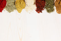 Colorful scattered powder seasoning in paper corners on white wooden board with copy space. Royalty Free Stock Images
