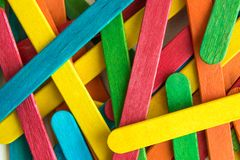 Colorful scattered wooden multicolored popsicle sticks. Colorful popsicle sticks background abstract minimal creative concept stock images