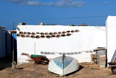Colorful Scene with dried fish and a Boat in front ATraditional Fishing Hut At A Remote Location On The Canary Islands. Fish dries in the sun of the canary Royalty Free Stock Photos