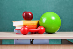 Colorful school accessories (apple, books, ball) on table Royalty Free Stock Photo
