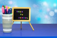 Colorful school equipment on dark blue table against light blue royalty free stock image