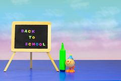 Colorful school equipment and a funny toy clown on dark blue tab stock images