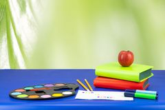 Colorful school equipment and two books on dark blue table again royalty free stock photos