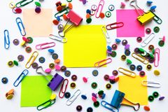 Colorful school and office supplies paper clips, pins, yellow notes, stickers on white background. Colorful stationary, back to school, office, business and stock photo