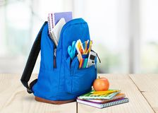 Colorful school supplies in backpack on blackboard. Back school backpack back to school art objects school background color Stock Photos