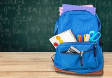 Colorful school supplies in backpack on blackboard. Back school backpack back to school art objects school background color Royalty Free Stock Photo