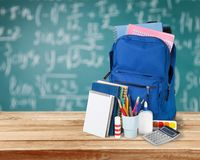 Colorful school supplies in backpack on blackboard. Back school backpack back to school art objects school background color Royalty Free Stock Photography
