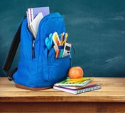 Colorful school supplies in backpack on blackboard. Back school backpack back to school art objects school background color Stock Photo