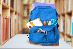 Colorful school supplies in backpack on classroom. Back school backpack back to school art objects school background color Stock Images