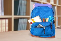 Colorful school supplies in backpack on classroom. Back school backpack back to school art objects school background color Royalty Free Stock Images