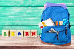 Colorful school supplies in backpack on wooden. Back school backpack back to school art objects school background color Royalty Free Stock Photos