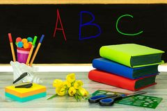 Colorful school supplies and books on the table in front of blackboard where are written the letters A, B, and C. Concept royalty free stock images