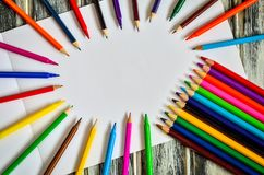 Colorful school supplies. Group of markers and crayons on a white paper royalty free stock image