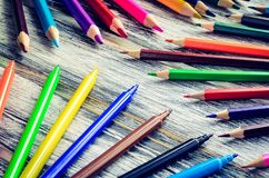 Colorful school supplies. Group of markers and crayons on a wooden table stock photo