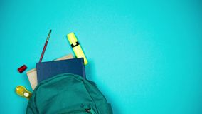 Colorful school supplies moving from school bag on blue background. Stop motion