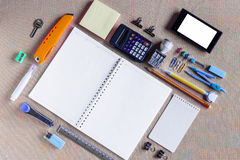 Colorful School Supplies Organized by Type Around Note Book Open to Blank Page Arranged Stock Photo