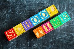 Colorful School time word from wooden blocks. On the wooden background Stock Image