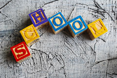 Colorful School word from wooden blocks. On the wooden background Royalty Free Stock Image