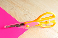 A colorful scissor that cut a zigzag pattern. With a pink paper illustrating the pattern Royalty Free Stock Photography