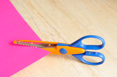 A colorful scissor that cut a zigzag pattern. With a pink paper illustrating the pattern Royalty Free Stock Image