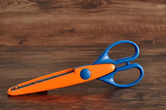 A colorful scissor that cut a zigzag pattern. On a wooden background Stock Photo