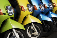 Colorful Scooters. A line of mopeds/scooters, gleaming and shiny. They look as if they are ready to go royalty free stock image