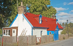 Colorful Scottish cottage. A Scottish cottage with corrugated red pained iron roof and blue porch and paintwork Royalty Free Stock Photos