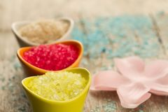 Colorful sea bath salts on wooden background. Royalty Free Stock Image