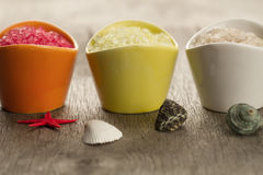 Colorful sea salts and seashells for the bathroom on wooden background. Royalty Free Stock Images