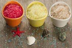 Colorful sea salts and seashells for the bathroom on wooden background. Royalty Free Stock Photo