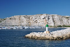 Colorful seascape on a clear sunny day: blue waters of the Mediterranean Sea and stone pier Stock Image