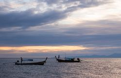 Colorful seascape with traditional thai boats with fishermen at evening fishing, scenic clouds and shadowy mountains in skyline. Andaman sea, Ao Nang, Krabi Stock Photos
