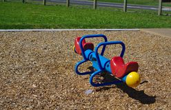Colorful seesaw on brown wooden pieces ground stock image